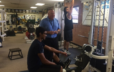 Mr. Ken Denning talks with Luis Deleon in the weight room on Wednesday.  Denning is enjoying his first few weeks as athletic director at West.
