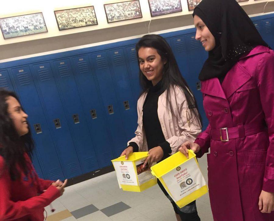Amiya Morales donates change to Interact Club members Rosie Carmona and Jana Sherif.