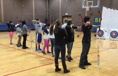 AP Physics students shoot arrows as part of an archery lesson in their class this week in the auxiliary gym.