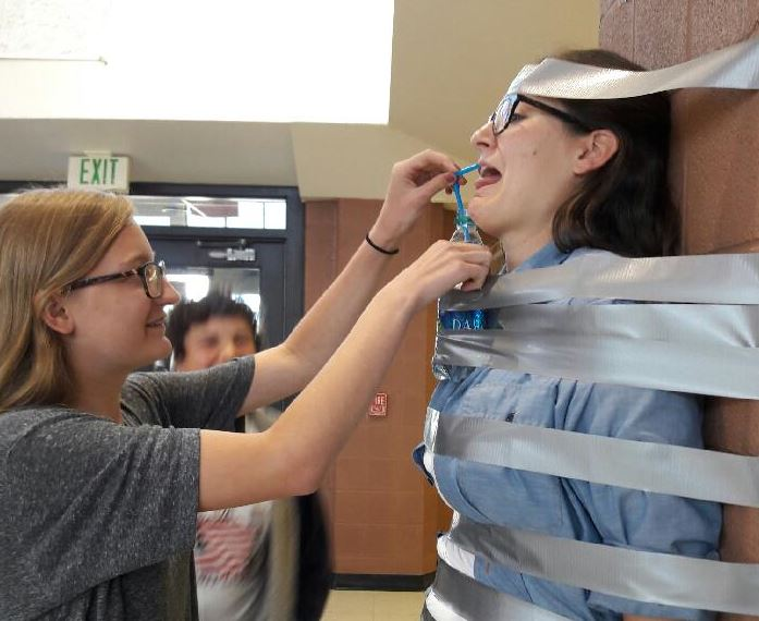 Ms.+Kelly+Stansbury+is+provided+water+from+freshman+Ava+Stephens+while+being+taped+to+a+wall+on+Tuesday.