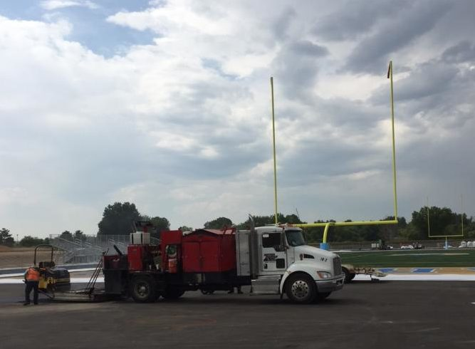 A maintenance truck is parked next to the new football field and track.  The project will be finished on September 18.
