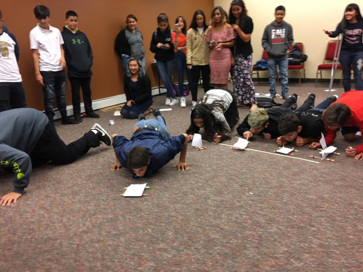 Freshman Caleb Sandoval blows his group's hand-made car across the floor during the AVID retreat on Wednesday.