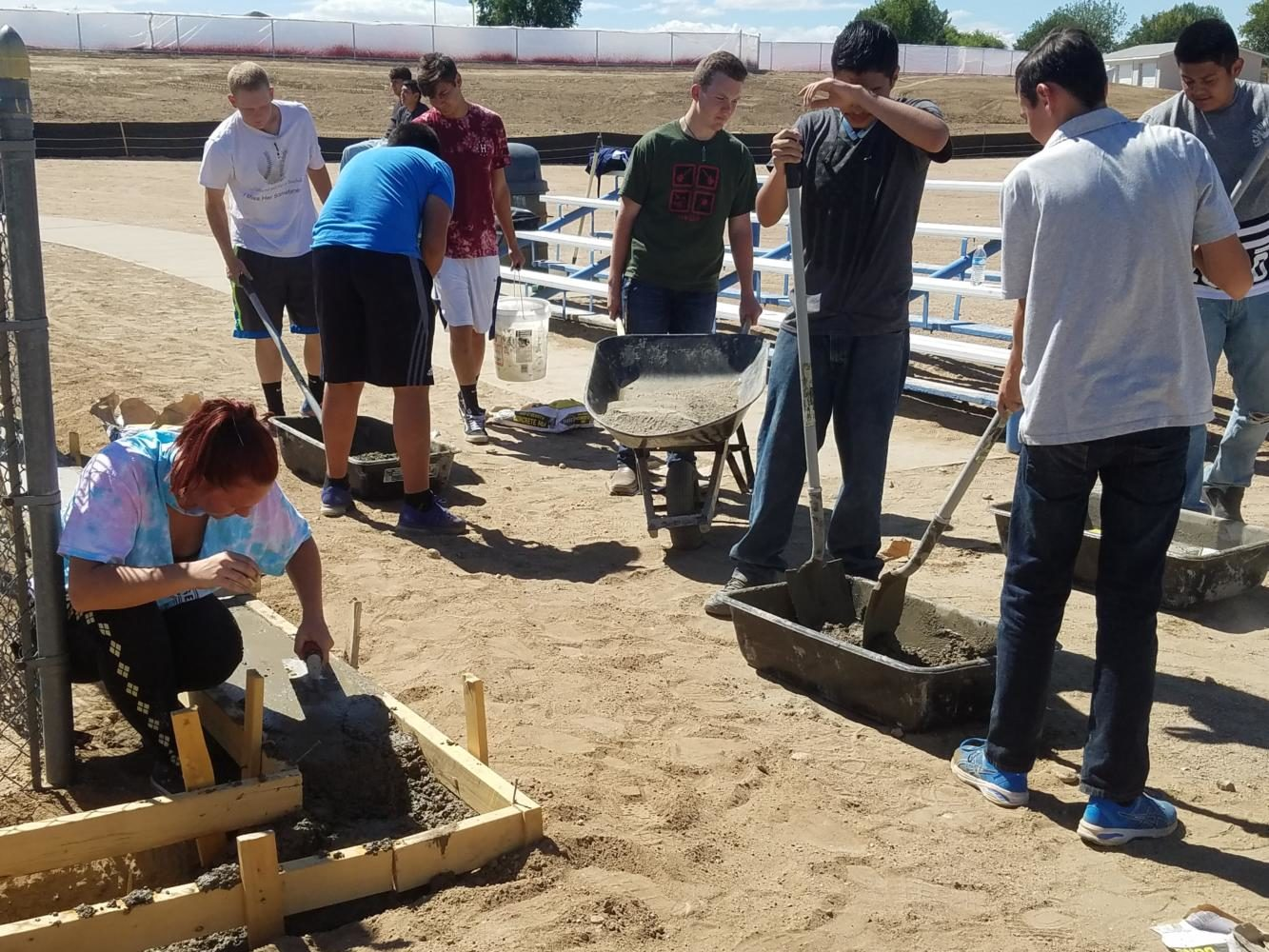 Junior Bryce Ewing pushes a wheelbarrow amidst other Construction Trades 2 students on Thursday as they laid cement for softball dugouts.