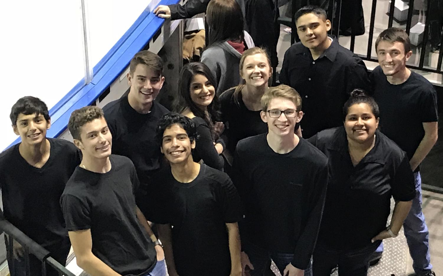 Greeley West choir members stand along the ice, waiting for their opportunity to perform the National Anthem at the Colorado Eagles game.