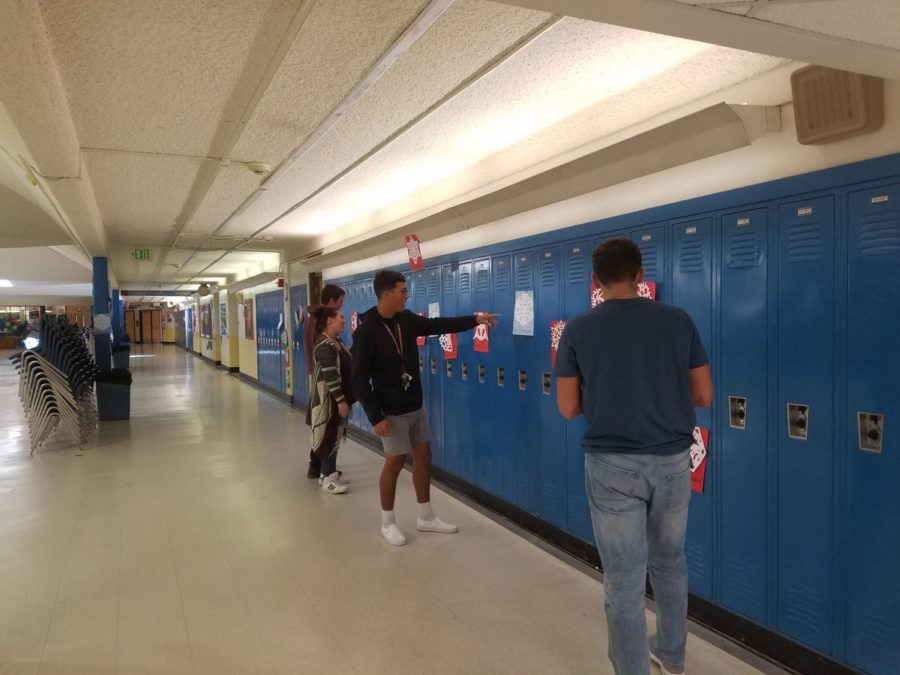 Sophomore Isaiah Torrez points to his snowflake in the hallway during school this week.