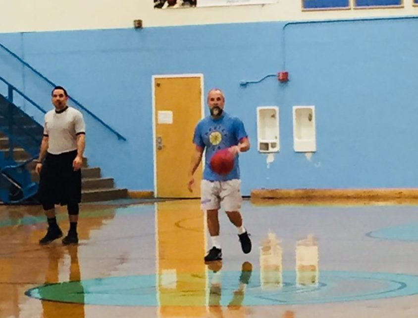 Mr. Brandon Torrez walks the ball back up court during the alumni basketball game.