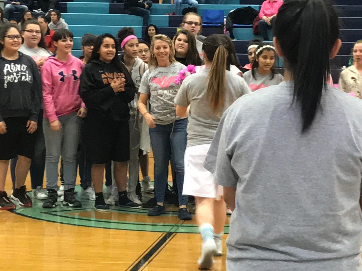 Brentwood Middle School teacher, Laurie Ford, is recognized with pink flowers by the girls basketball team before Tuesday nights game at Greeley West.
