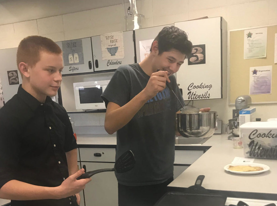 Freshmen Dillon Fenton and Joshua Hernandez Manriquez make crepes with French Club.