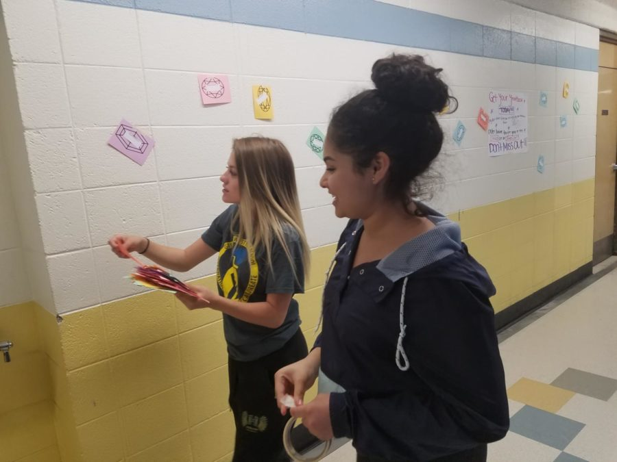The yearbook staff hangs gemstones of student names on walls.  The yearbook staff is hoping for increased sales by giving away books through competitions.