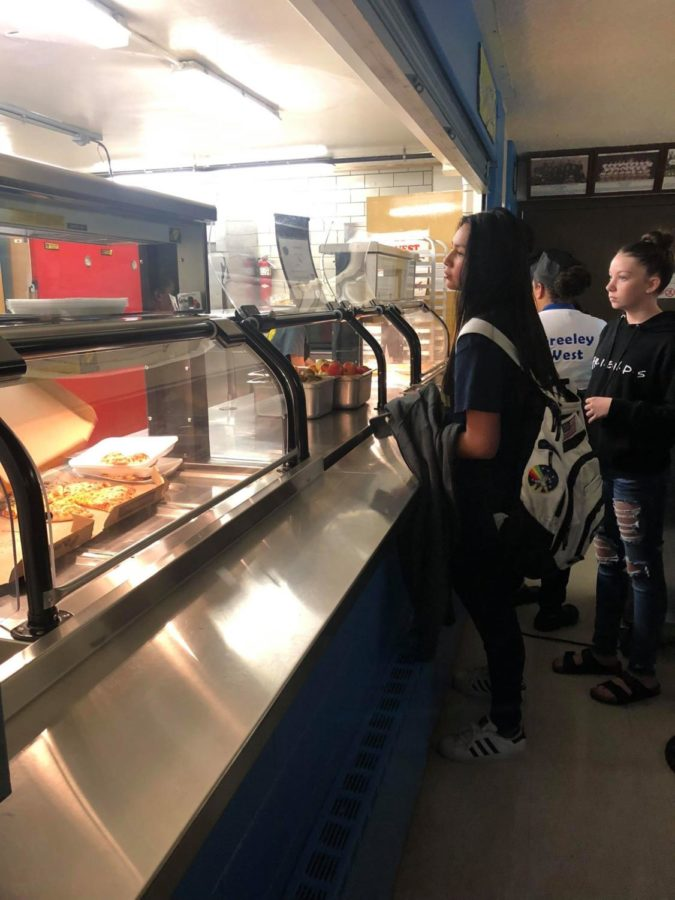 Greeley West freshman Melyssa Camacho waits in line for pizza on Friday afternoon.