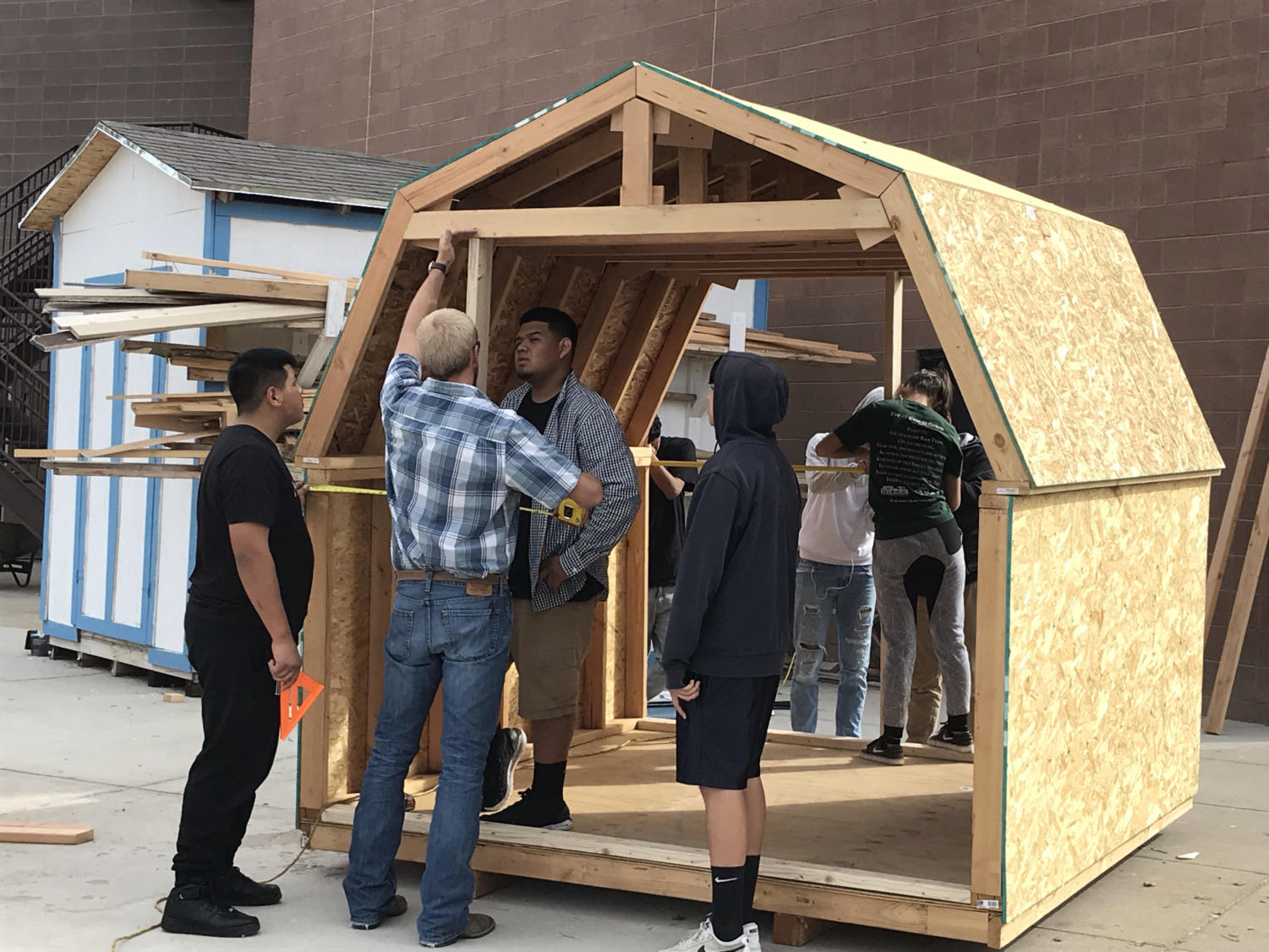 Mr. Jordan Karlberg instructs his students as they build a shed.