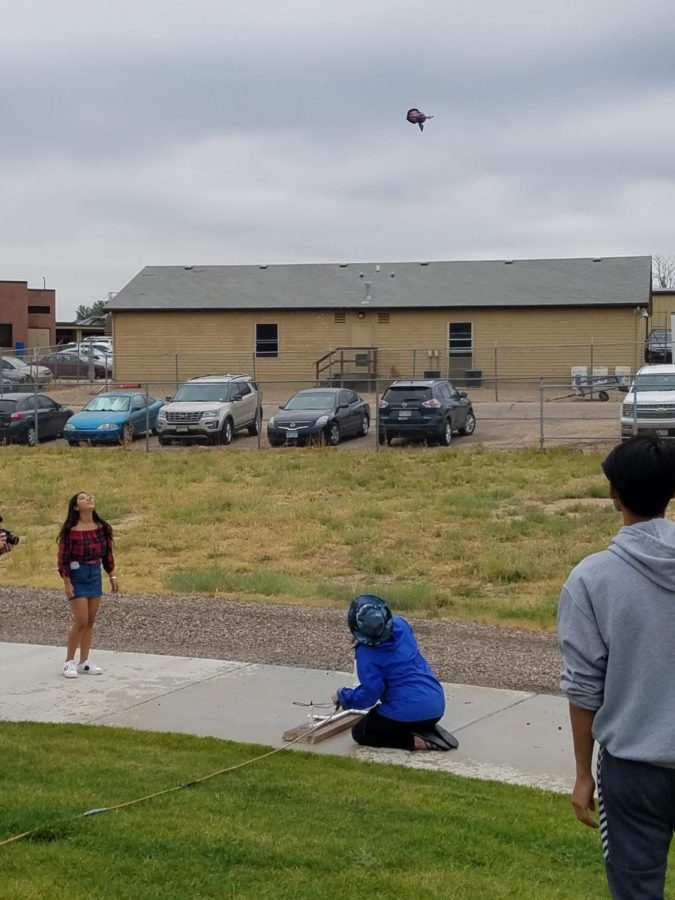 Sculpture teacher Ms. Dawn Feinberg launches a student's rocket on Friday morning as part of the first sculpture project of the year.