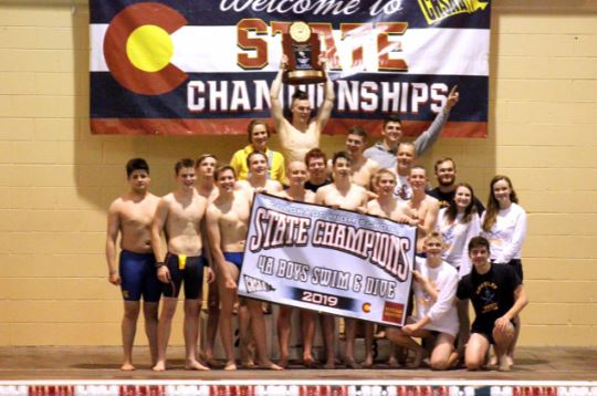 The Greeley West boys swimming team celebrates their championship in a team photo.