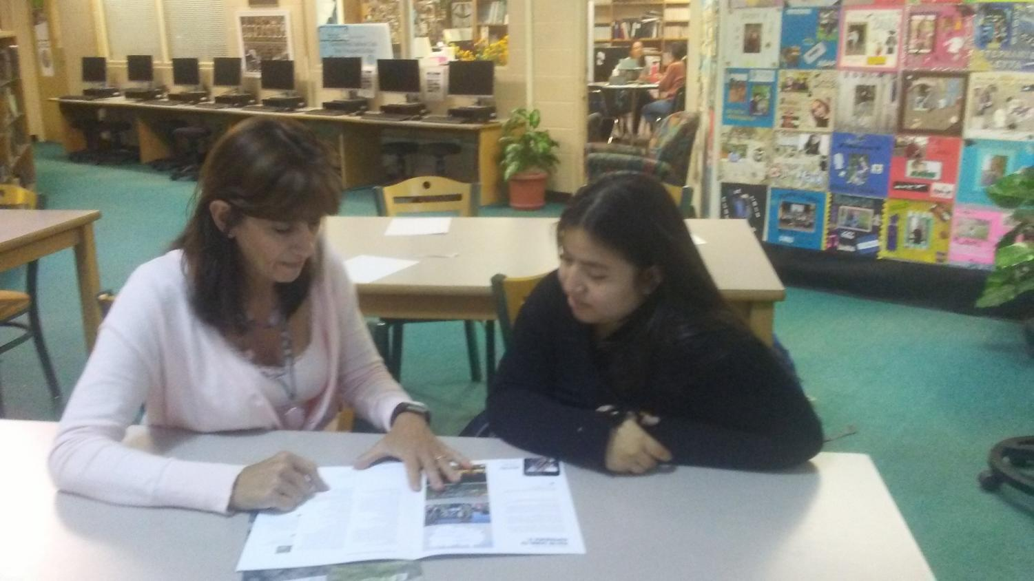 Ms. Susan Eastin and Daniela Adame Salomon discuss a future trip abroad in the library last week.