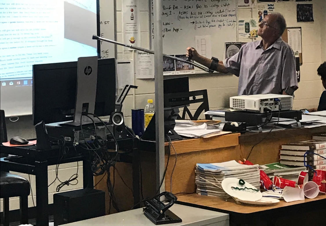 Mr. Richard Dufault points to the screen using his crutch during class on Monday.  Dufault returned to work last week after suffering a broken leg during a biking accident.
