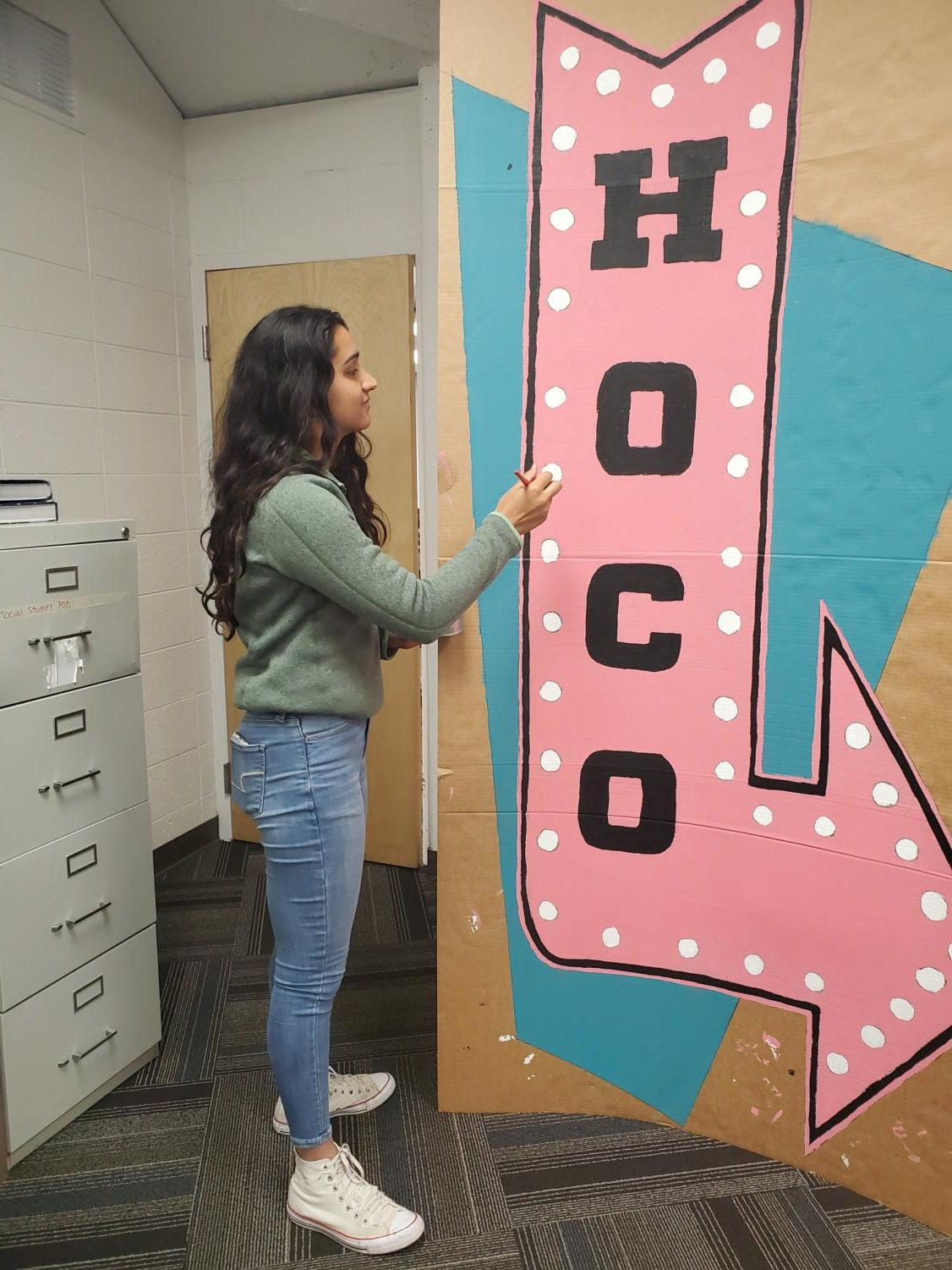 STUCO Grace Chahal preps a Homecoming banner in preparation for Saturday's dance.