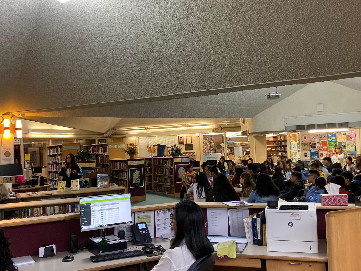 Los Angeles-based Chicana poet and activist, Angela Aguirre, left, addresses the audience while sophomore AVID students listen to her.