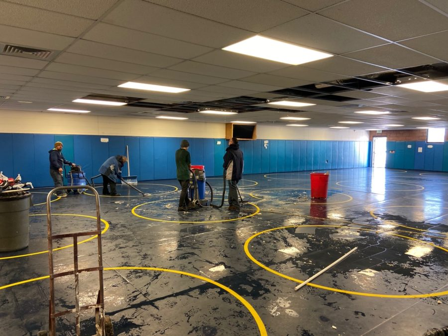 Greeley West staff members rush to mop up  water that flooded the wrestling room after a pipe burst on Wednesday afternoon.