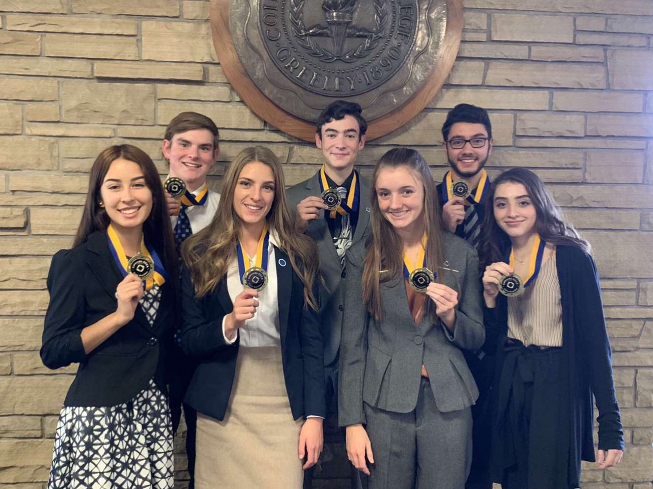DECA students look spiffy posing with their medals after qualifying for the state competition