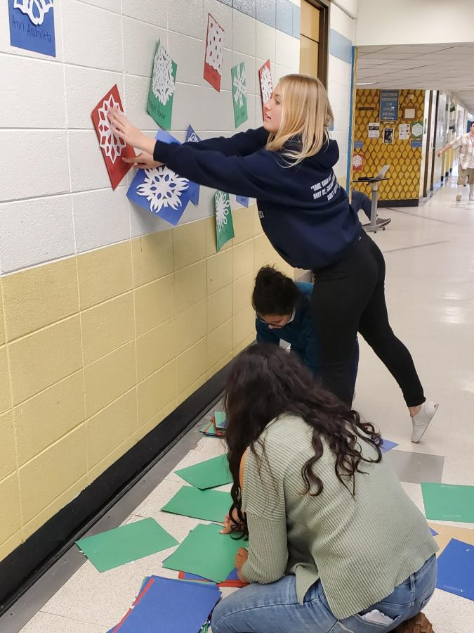 Senior Kendra Roth tapes snowflakes to the walls earlier this month, continuing a tradition that goes back decades.