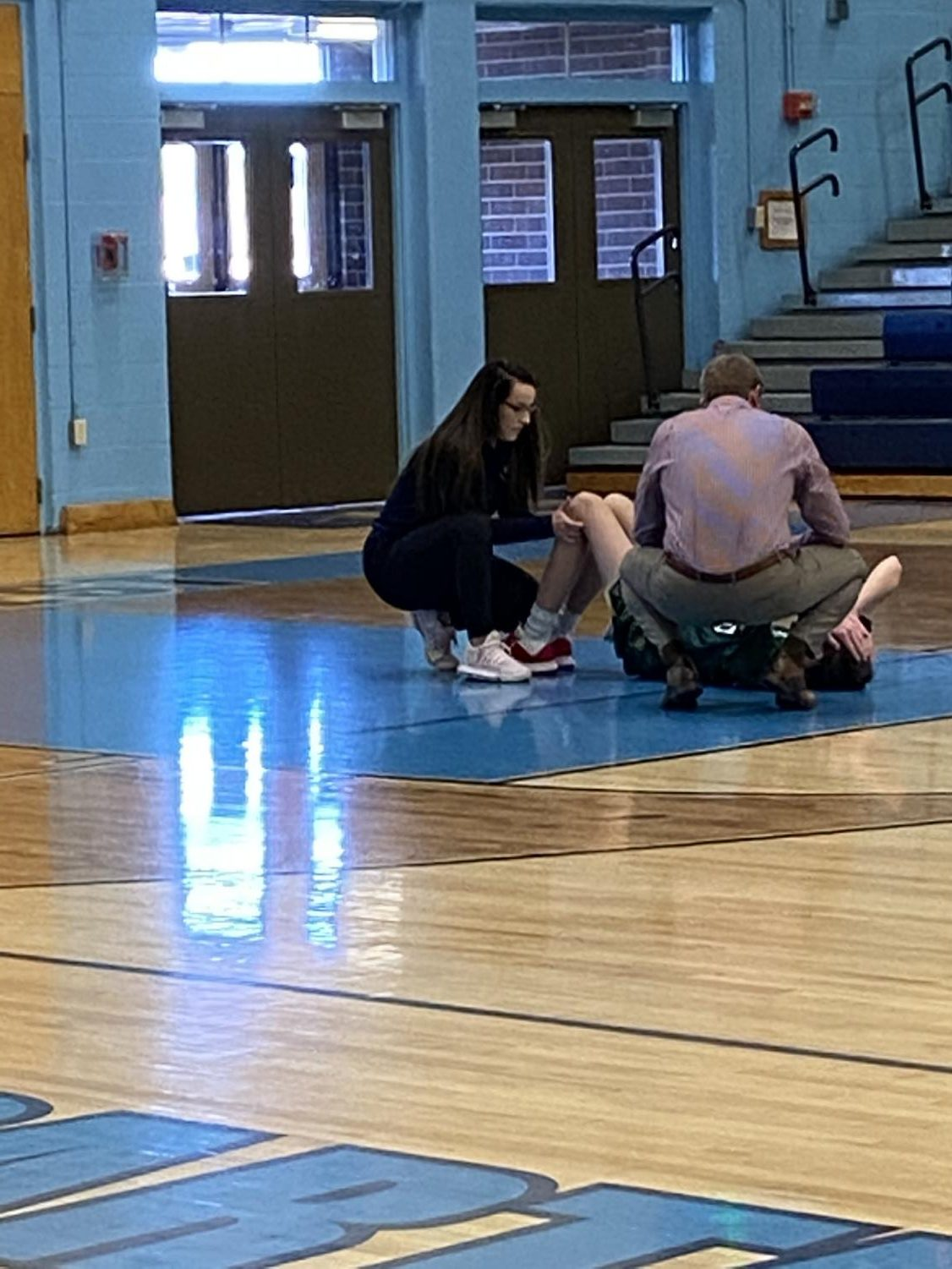 Greeley West trainer Ali Curtis works with a Mountain Vista student who appeared to hyper-extend his knee during the JV basketball on Saturday.