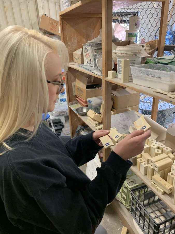 Junior Ashlyn Estal examines her clay tiles used in her science fair project that combines her love of art with her science class.