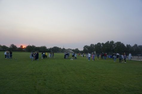 Seniors mingle as the sun rises on Thursday August 20.  Of course, the sprinklers came on.