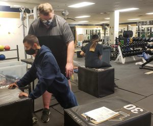 Greeley West PE teacher Mr. Ryan Walstrom works with senior Jake Horner on Monday.  In addition to teaching his classes, Walstrom is working as an administrative intern as he works toward his administration license.