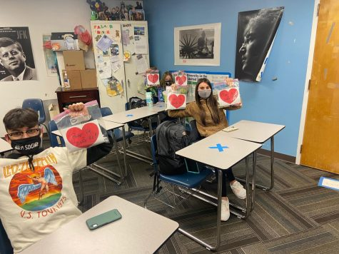 "AVID Students Mateo Vasquez, Camille Musil and Bailey Schiller hold up their ""Pucker Up & Buckle Up"" bags before delivering them to homerooms on Friday."