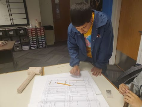 Sophomore Enrique Lugo analyzes a blueprint in his construction trades class. Construction trades is making adjustments to its curriculum as it is housed in a classroom this year.